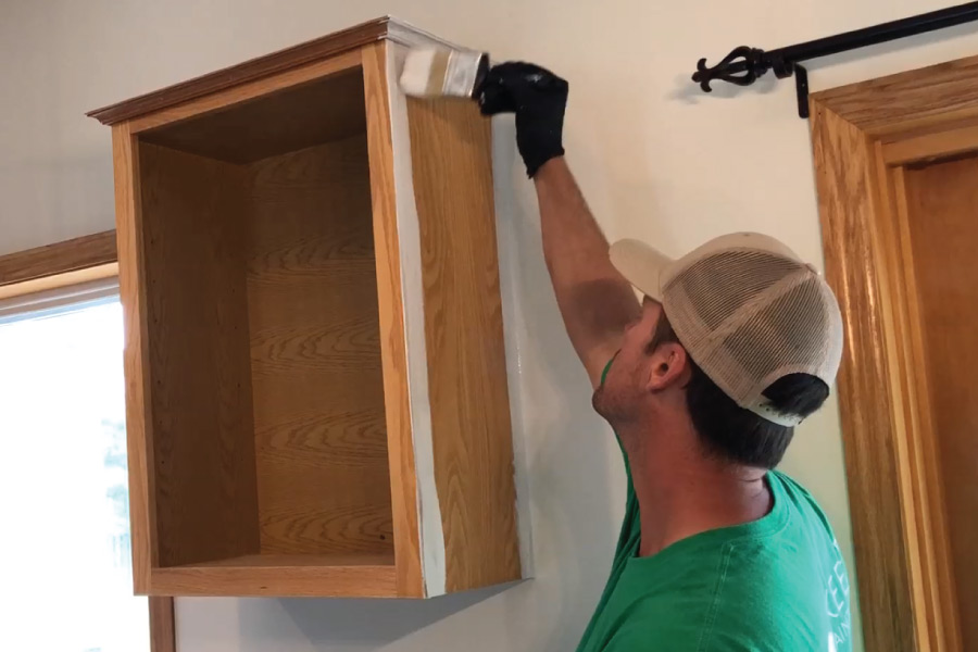 Brush and roll application of oil primer to cabinet boxes
