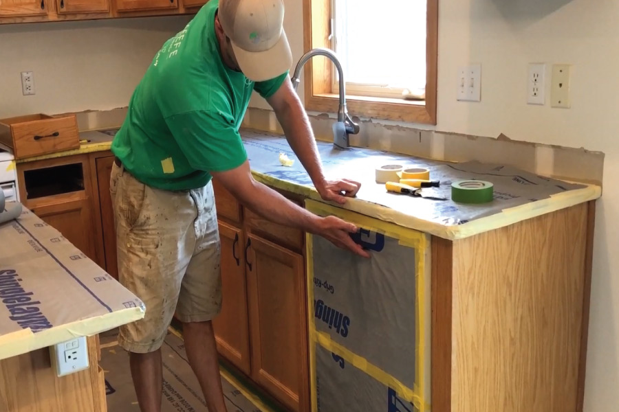 Masking appliances before painting cabinets in Apple Valley