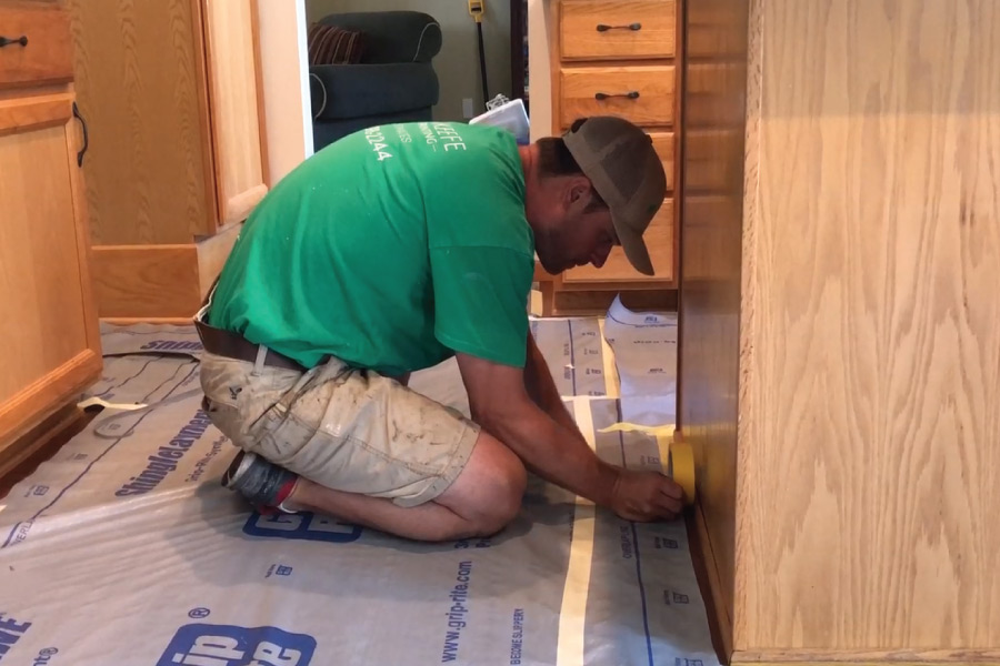 Using yellow frog tape along edges to cover floors