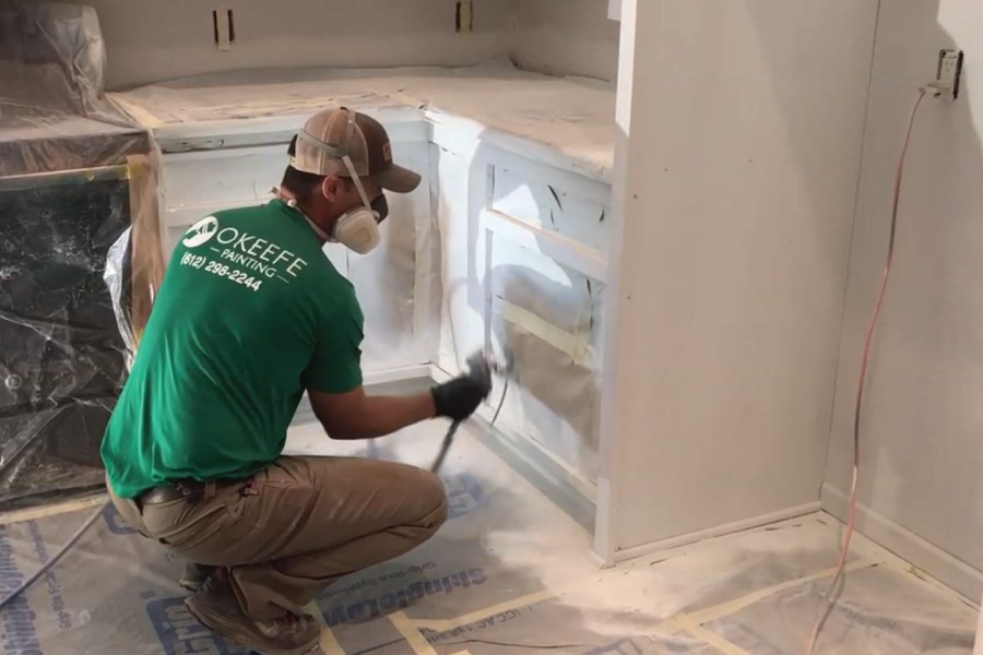 Spraying cover stain oil primer on cabinets with airless sprayer
