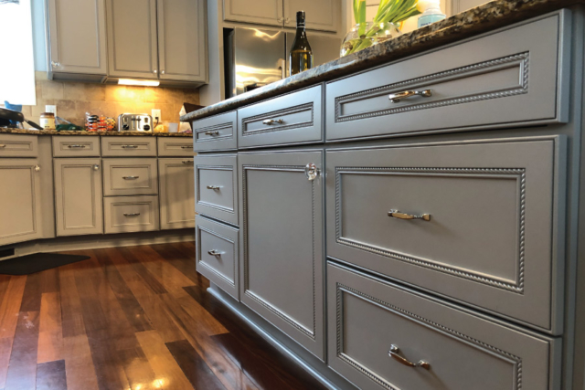 New hardware and fresh paint on these newly refinished kitchen cabinets