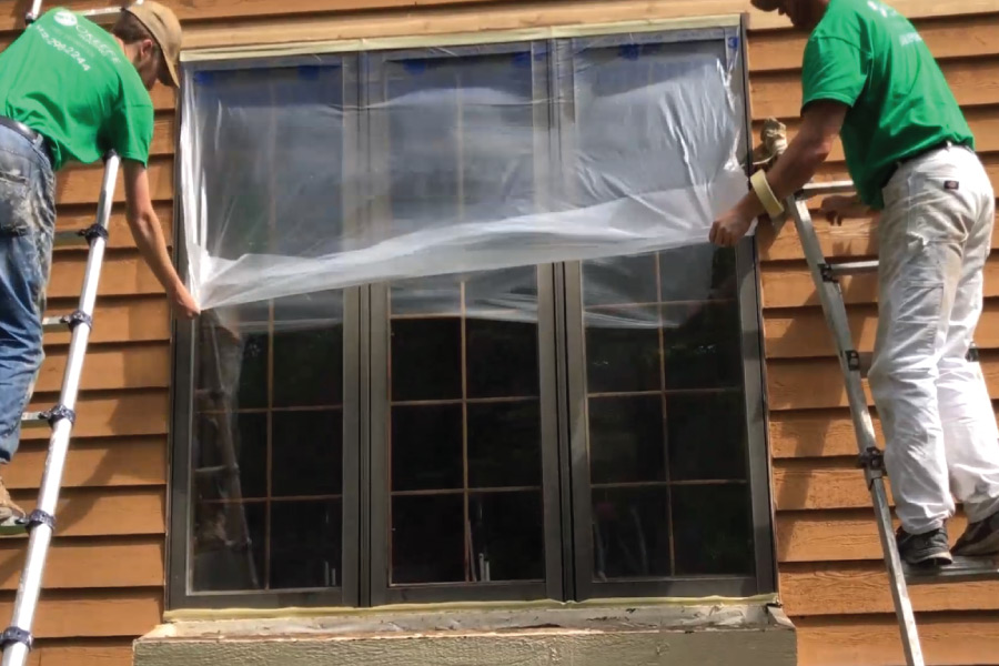 Covering exterior windows with plastic before painting