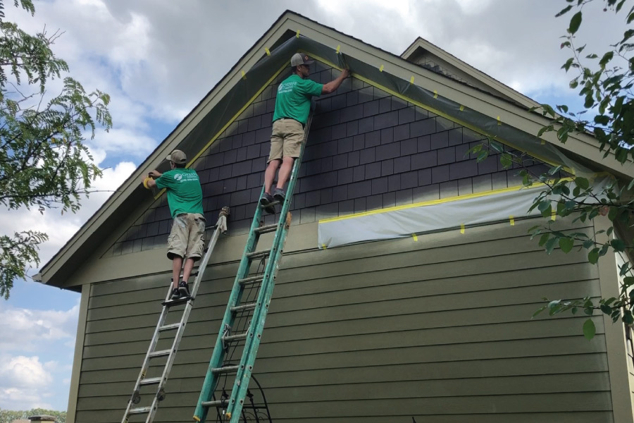 Masking soffits before painting shakes on this Rosemount Home