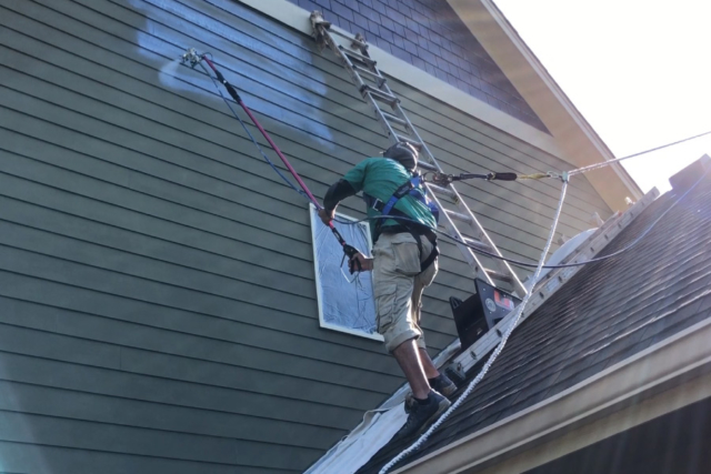 Painter spraying on roof using spray extension