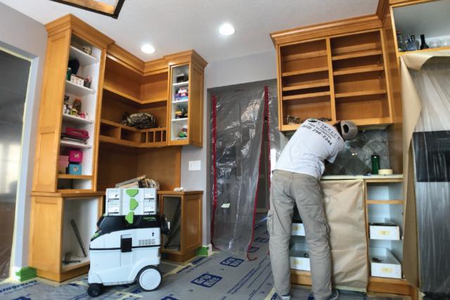 Okeefe painting employee protecting backsplash before painting cabinets